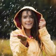 Stock Photo: Pretty young womin yellow raincoat