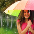 Beautiful woman under rainbow umbrella — Stock Photo