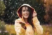 Mooie jonge vrouw in gele regenjas — Stockfoto