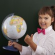 Schoolgirl with globe showing ok sign — Stock Photo #30562167