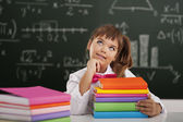 Cute little schoolgirl sitting in classroom with her books and dreaming — Stock Photo