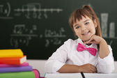 Cute little schoolgirl sitting in classroom with her books — Stock Photo