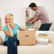 Beautiful woman resting on couch while her husband decorating their new living room — Stock Photo