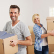 Couple carrying cardboard boxes in new home — Stock Photo