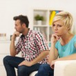 Unhappy young couple sitting in living room  — Stock Photo