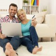 Happy loving couple sitting on the floor and using laptop and showing credit card — Stock Photo