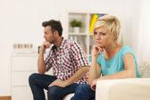 Niezadowolony młoda para siedzi w salonie — Zdjęcie stockowe