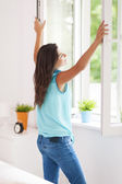 Young woman opening window — Stock Photo