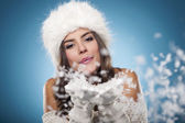Beautiful winter woman blowing snow — Stock Photo