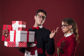 Rude nerdy man with christmas gifts — Stock Photo