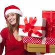 Woman wearing santa hat holding christmas gifts and credit card — Stok fotoğraf