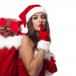 Sexy woman giving christmas gifts from sack of santa claus — Stock Photo