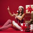Smiling and sexy santa claus woman showing — Stock Photo