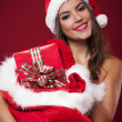 Smiling sexy woman holding sack full of christmas gifts — Stockfoto