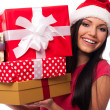Woman wearing santa hat holding stack of christmas gifts  — Foto de Stock
