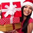 Woman wearing santa hat holding stack of christmas gifts  — Стоковая фотография