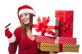 Woman wearing santa hat holding christmas gifts and credit card — Stock Photo