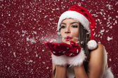 Beautiful santa claus woman blowing snowflakes — Stock Photo