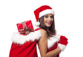Woman wearing santa claus clothes holding sack full of christmas gifts — Stock Photo