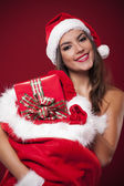 Smiling sexy woman holding sack full of christmas gifts — Stock Photo