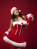Beautiful woman holding small red christmas gift — Foto Stock