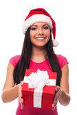 Cute woman with santa hat giving christmas gift — Stock Photo