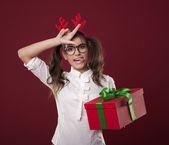 Nerdy woman with christmas gift showing loser sign — Stok fotoğraf