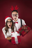 Surprise nerd couple holding christmas gifts — Stock Photo