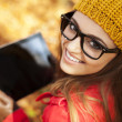Smiling young woman using digital tablet  — ストック写真