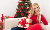 Blonde woman sitting on sofa — Stockfoto