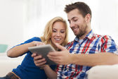 Smiling couple using digital tablet at home — Foto Stock