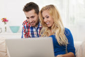 Smiling couple using laptop at home — Stock Photo