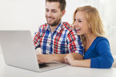 Laughing couple using computer at home — Stock fotografie