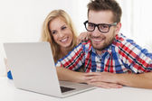 Smiling couple with laptop — Stock Photo