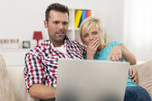 Shocked couple looking at laptop — Stock Photo