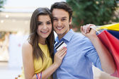 Couple with credit card and shopping bags — Stock Photo