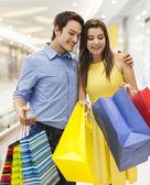 Couple peeking into the shopping bag — Stock Photo