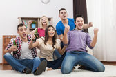 Friends watching TV and cheering soccer — Stock Photo