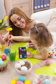 Mother and her baby painting easter eggs — Стоковое фото