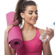 Woman with water and exercise mat — Stock Photo #43757113