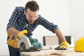 Carpenter sawing wood board — Stock Photo
