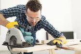 Carpenter cutting wooden plank — Stock Photo