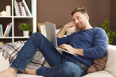 Man using laptop at home — Stock Photo