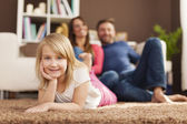 Girl relaxing with her parents at home — Stock Photo