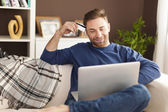 Man with credit card buying online — Stock Photo