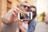 Couple taking selfie in the city — Stockfoto
