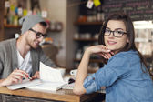Woman studying with her friend at cafe — Stock Photo