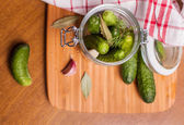 Cucumbers in rustic jar — Stock Photo