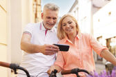 Mature couple using mobile phone — Stock Photo