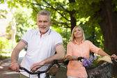 Mature couple cycling in park — Stock Photo